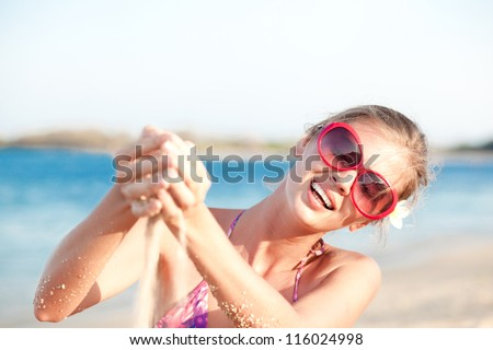 attractive woman sieving sand through hands on tropical beach