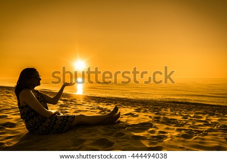 Attractive woman silhouette sitting on the beach at sunset in the summer