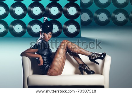 Attractive woman siting in white chair on vinyl records background - stock photo