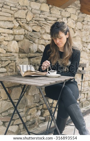 Attractive woman sitting at a rustic wooden table enjoying a relaxing cup of coffee and reading