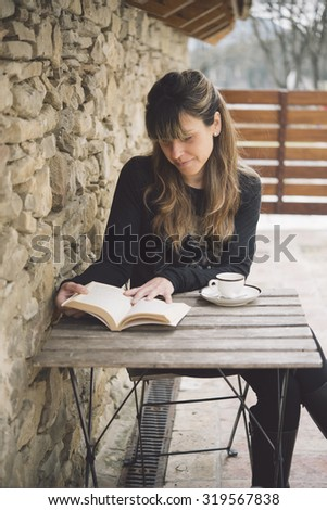 Attractive woman sitting at a rustic wooden table enjoying a relaxing cup of coffee and reading - stock photo