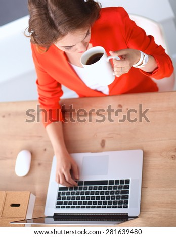 Attractive woman sitting at desk in office, working with laptop  - stock photo