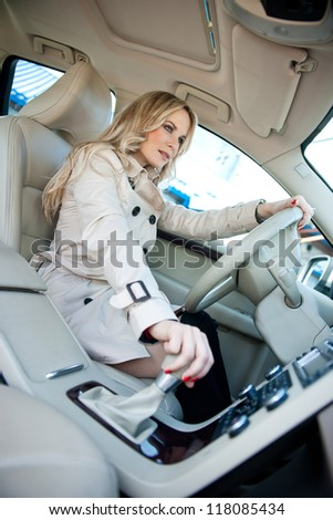 attractive woman sitting in car driver seat - stock photo