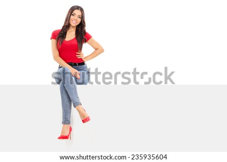 Attractive woman sitting on a blank billboard isolated on white background - stock photo
