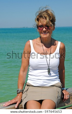 Attractive Woman Sitting on a Boardwalk at the Beach