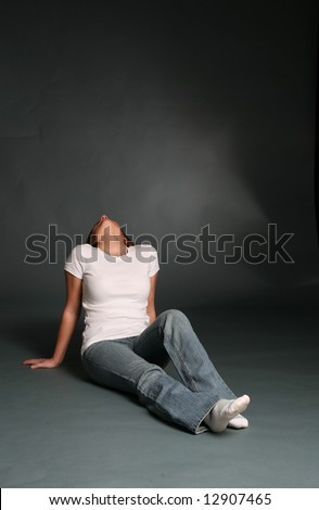Attractive woman sitting with her head thrown back. - stock photo