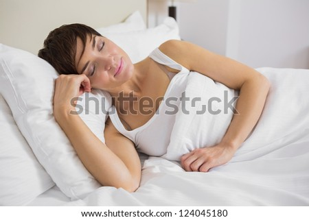 Attractive woman sleeping in bed in hotel room - stock photo