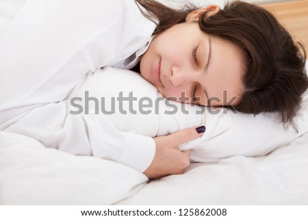 Attractive woman sleeping peacefully with her hand tucked under the pillow as she enjoys sweet dreams - stock photo