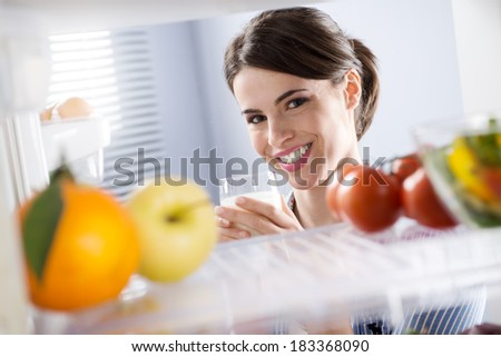 Attractive woman smiling and holding a glass of milk in front of refrigerator. - stock photo
