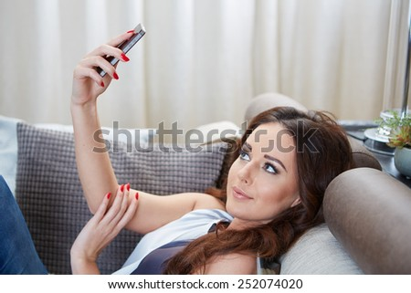 Attractive woman smiling as she reads an sms message on her mobile while relaxing barefoot on a sofa in her living room - stock photo