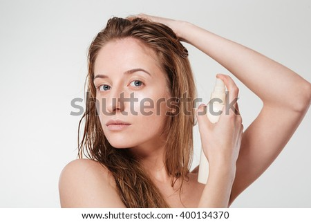 Attractive woman spraying hairspray isolated on a white background - stock photo