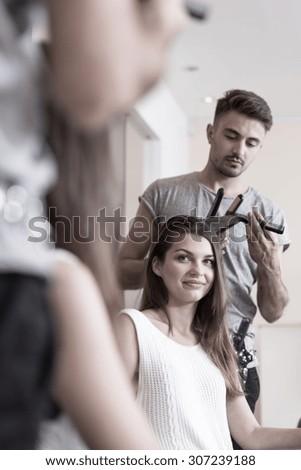 Attractive woman straightening hair in hairdresser salon - stock photo