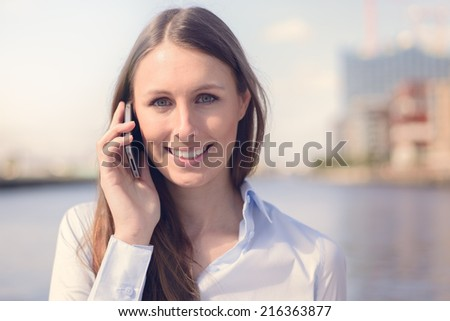 Attractive woman taking a call on her mobile phone standing outdoors against a river background smiling at the camera as she listens to the conversation