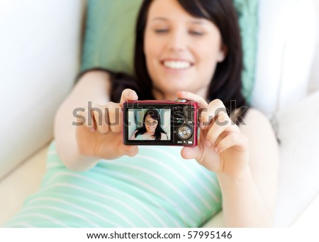 Attractive woman taking a picture of herself lying on bed at home - stock photo
