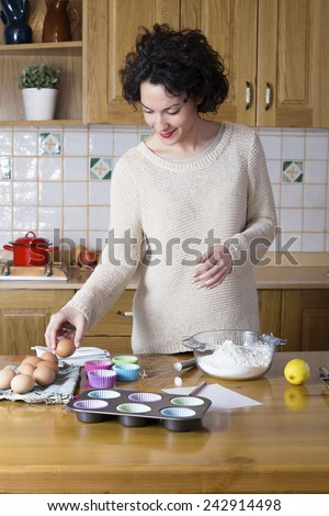 Attractive woman taking an egg to make a cupcakes recipe. Modern housewife cooking homemade traditional cupcakes in a rustic kitchen - stock photo