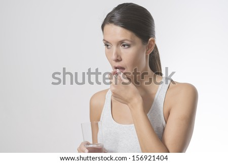 Attractive woman taking medication holding a glass of water in one hand as she slips a tablet or antibiotic into her mouth to treat an illness, or a painkiller or supplement - stock photo