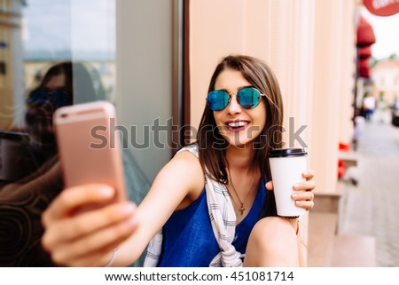 Attractive woman taking photo with take-out coffee on her phone
