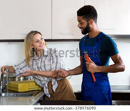 Attractive woman thanking black professional plumber for work. Focus on the woman