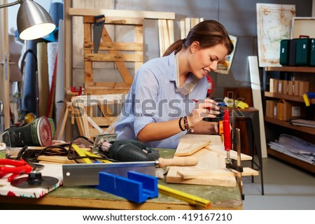 Attractive woman tinkering in home workshop. - stock photo
