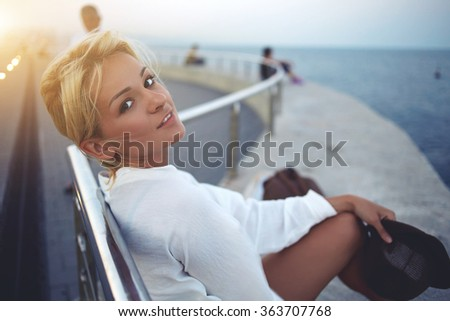 Attractive woman tourist looking at camera while sitting on a sea pier during rest after walking in an unfamiliar city, pretty female enjoying warm summer evening during her long-awaited vacation - stock photo