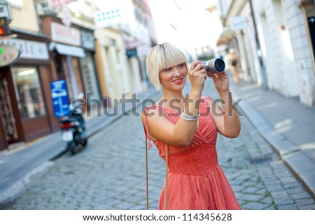 attractive woman tourist with camera taking pictures in old city street - stock photo