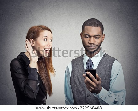 Attractive woman trying to bring attention of young handsome man ignoring her looking skeptical at smartphone reading browsing internet grey wall background. Phone addiction concept. Face expression - stock photo