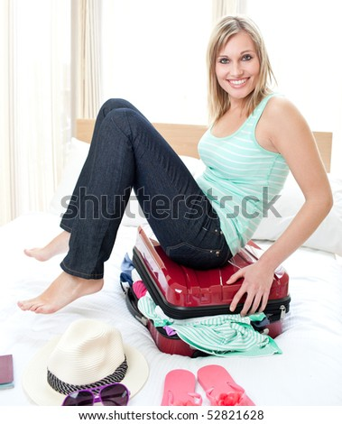 Attractive woman trying to close her suitcase on her bed - stock photo