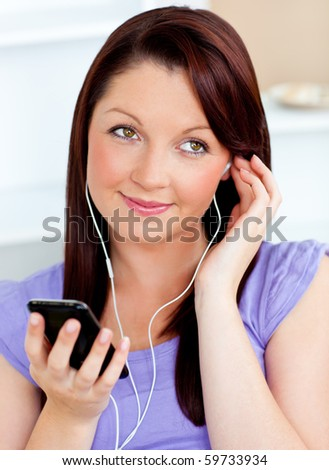 Attractive woman using her cellphone to listen to music with earphones at home