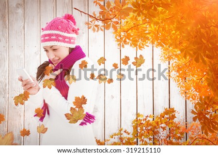 Attractive woman using her smartphone against autumn leaves on wood