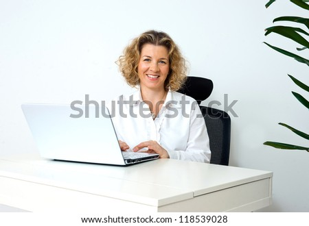 attractive woman using laptop at her office desk - stock photo