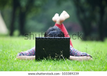 Attractive woman using laptop in the park lying on the green grass