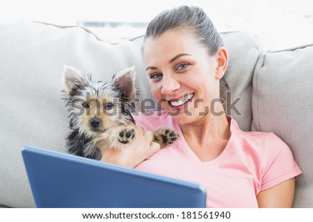 Attractive woman using tablet pc with her yorkshire terrier at home in the living room - stock photo