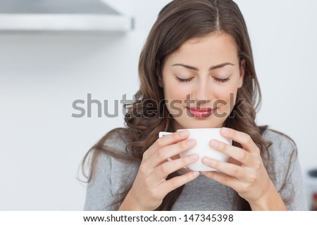Attractive woman waking with the smells of coffee - stock photo