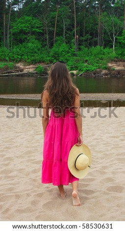 Attractive woman walking at the shoreline - stock photo