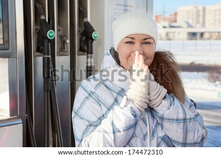 Attractive woman warming hands in petrol station at winter - stock photo