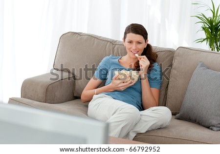 Attractive woman watching television and eating pop corn on the sofa at home - stock photo