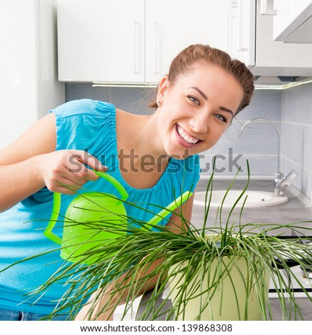 attractive woman watering flowers at home - stock photo