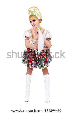 Attractive woman wearing a folk russian dress dancing against isolated white background