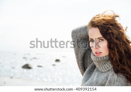 Attractive woman wearing a warm cardigan at the cold beach. Stock image. - stock photo