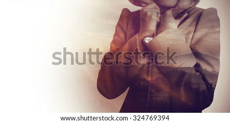 Attractive woman wearing a warm coat with hood raised against trees and mountain range against cloudy sky - stock photo