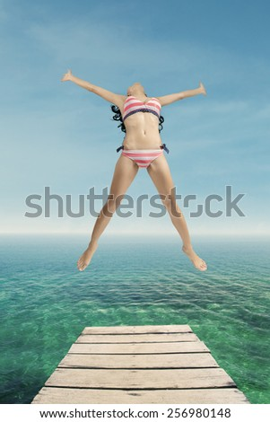 Attractive woman wearing swimsuit and jump on the pier, shot at tropical beach - stock photo