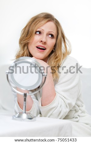 Attractive woman wearing white bathrobe sitting in front of a small round mirror