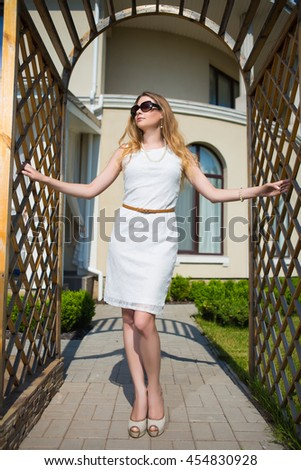 Attractive woman wearing white dress and sunglasses posing in archway - stock photo