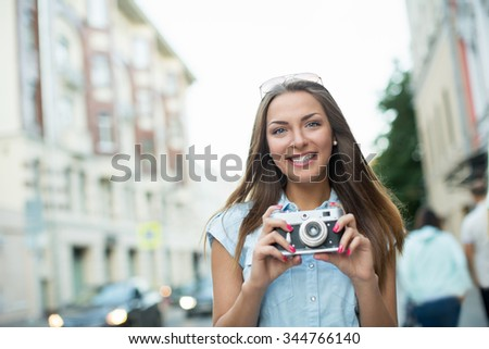 Attractive woman with a camera outdoors - stock photo