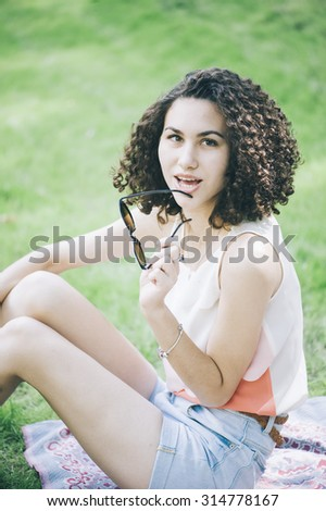 Attractive woman with a curly hair is having a picnic in the park.