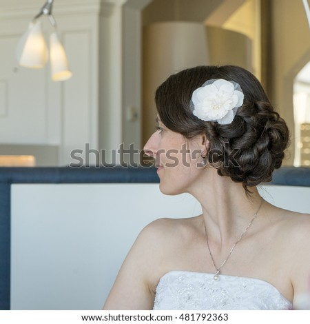 Attractive woman with a festive hairstyle and flower in her hair / attractive women / Hairstyle