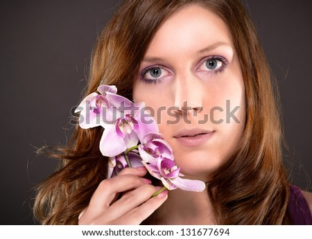 attractive woman with a orchid and beautiful makeup - stock photo