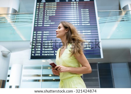 Attractive woman with a passport at the board - stock photo