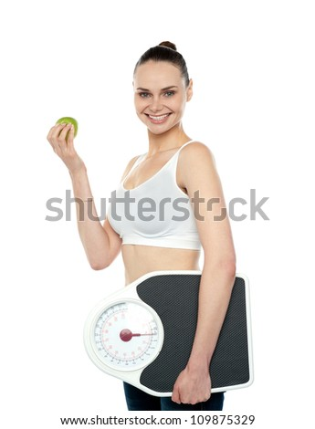 Attractive woman with apple and weight scale smiling at camera