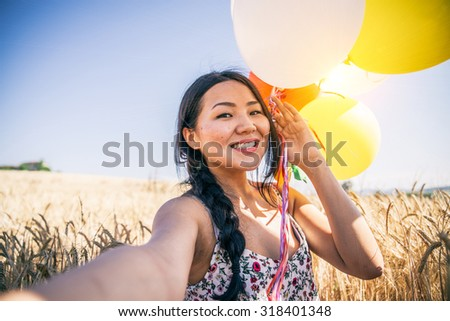 Attractive woman with balloons and selfie stick taking a self portrait in a wheat field - Pretty asian girl smiling and having fun outdoors - stock photo